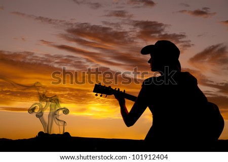 A woman is sitting with a guitar in the sunset by a camp fire.
