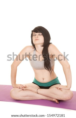 A woman is sitting with her legs crossed and eyes closed. - stock photo