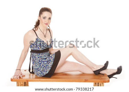 A woman is sitting with her legs up on a bench, wearing a dress.