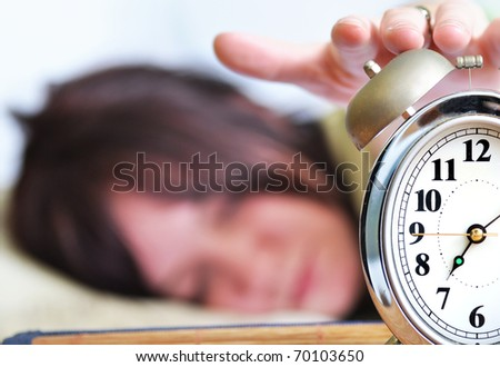A woman is sleeping with an alarm clock in front - stock photo