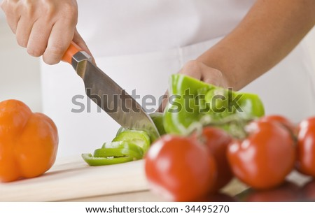 A woman is slicing produce in a kitchen.  Horizontally framed shot. - stock photo