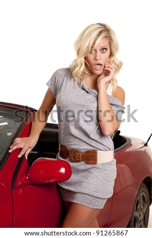 A woman is standing by her red car with a shocked expression on her face.