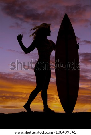 A woman is standing by her surf board silhouetted in the sunset. - stock photo