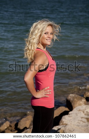 A woman is standing by the water with a smile. - stock photo