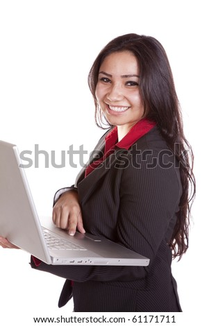A woman is standing holding a laptop and smiling.