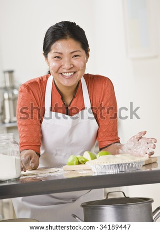 A woman is standing in a kitchen and slicing apples for a pie.  She is looking away from the camera.  Vertically framed shot. - stock photo