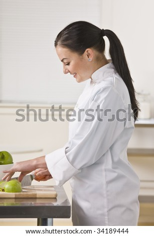 A woman is standing in a kitchen and slicing apples.  She is looking away from the camera.  Vertically framed shot. - stock photo