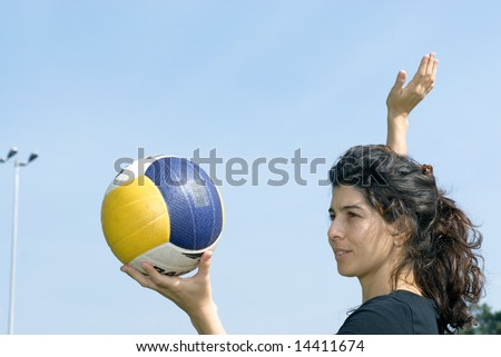 A woman is standing in a park.  She is looking away from the camera.  She is about to spike a volleyball.  Horizontally framed photo. - stock photo