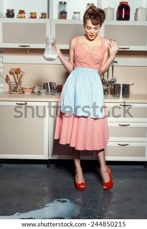 A woman is standing in the kitchen and looks at the floor. On the floor, spilled milk.