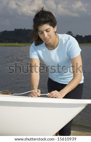A woman is standing next to a sailboat on the water.  She is tying a knot in a rope, smiling, and looking down at the rope.  Vertically framed shot. - stock photo