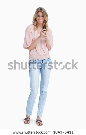 A woman is standing up smiling at the camera and holding a mobile phone against a white background - stock photo