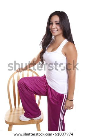 A woman is standing with one foot on a chair. - stock photo
