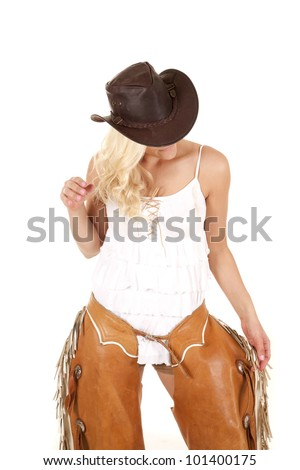 A woman is standing with one hand on her chaps the other hand by her hair. - stock photo
