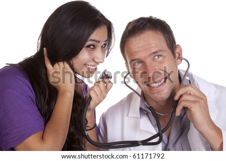 A woman is talking into a stethoscope and her doctor is smiling. - stock photo