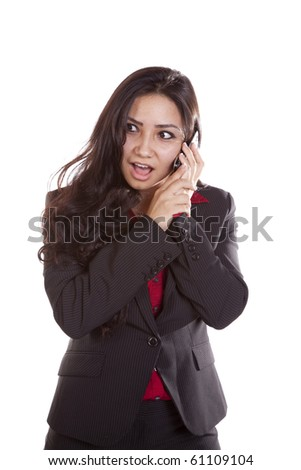 A woman is talking on her phone with a surprised expression on her face. - stock photo