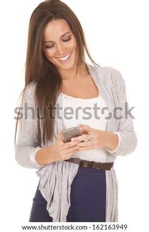 A woman is texting and smiling at her phone. - stock photo
