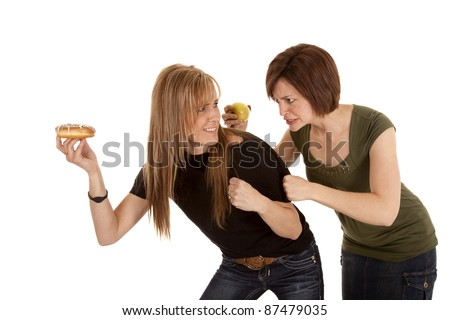 a woman is trying to fight the other woman for her doughnut - stock photo