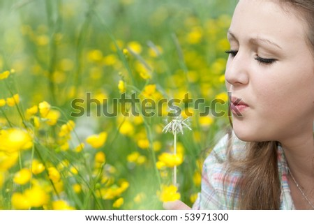 A woman is trying to sprinkle the seeds of a flower