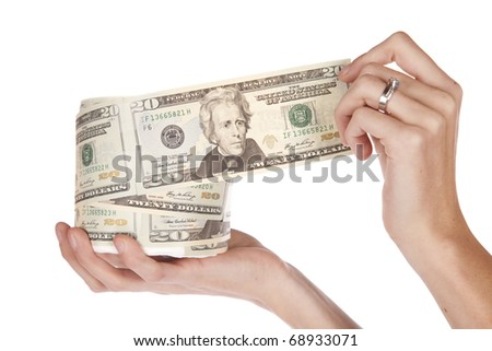 A woman is unrolling a big roll of money. - stock photo