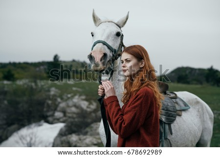 A woman is walking with a horse