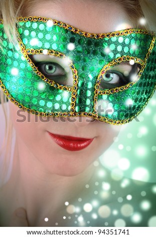 A woman is wearing a costume mask with green sparkles. Use it for a party, carnival or Halloween concept.