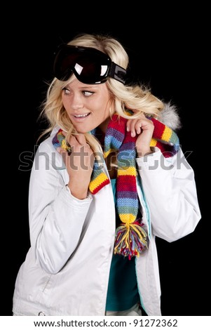 A woman is wearing a white coat with a scarf and goggles. - stock photo