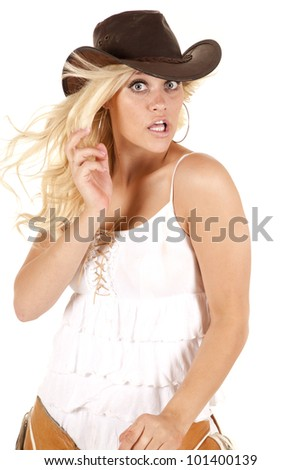 A woman is wearing chaps and has a shocked look on her face. - stock photo