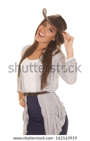 A woman is winking while holding the brim of her hat. - stock photo