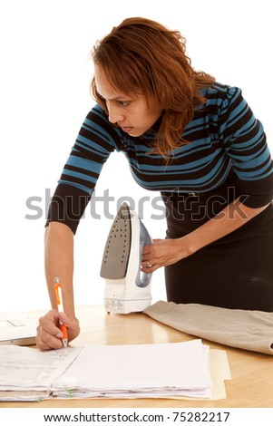 A woman is working and doing house work at the same time.