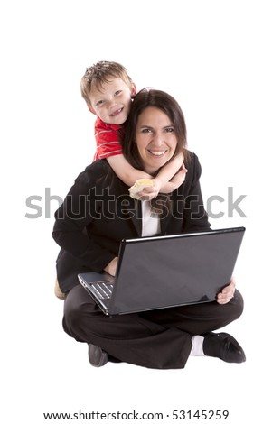 A woman is working on her laptop while her son reaches around her neck with a sandwich.