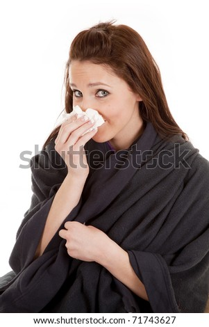 A woman is wrapped in a warm blanket and has a tissue. - stock photo