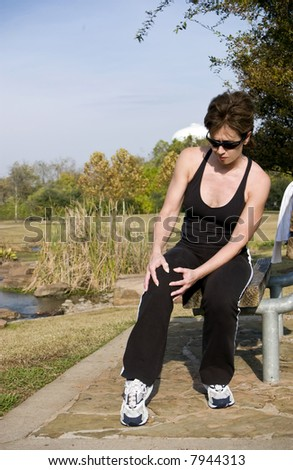 A woman jogger holding her knee as if in pain. - stock photo