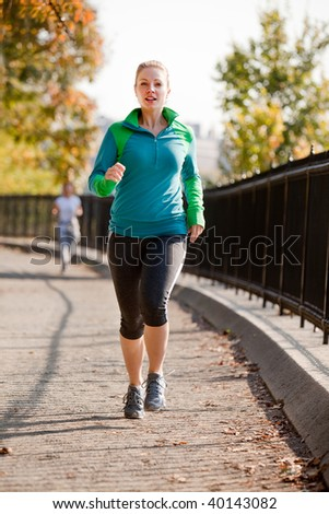 A woman jogging in a park - stock photo