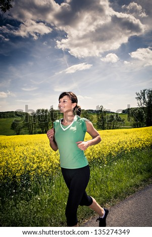 A woman jogging in front of cross country - stock photo