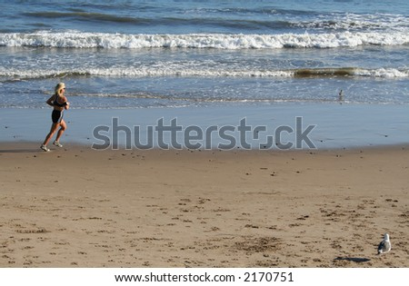 A woman jogging on the beach.