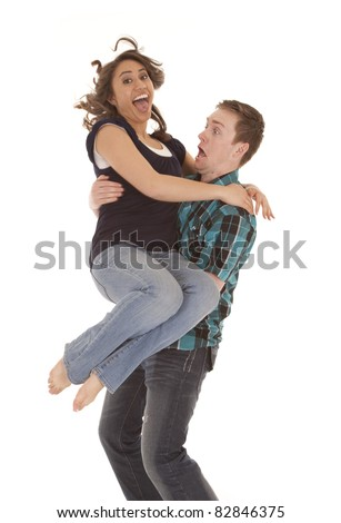A woman jumping into her mans arms with funny expressions on their faces. - stock photo