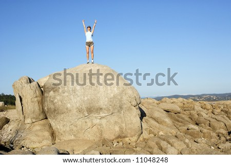 A woman jumps for joy when she reaches the top of the hill