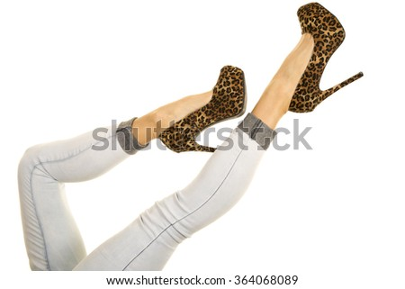 a woman kicking up her legs with her cheetah print shoes in the air.