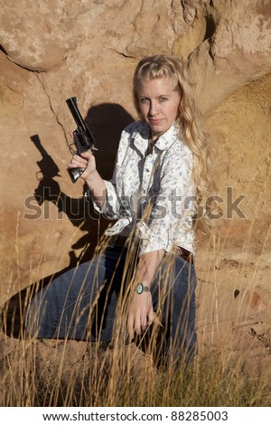 A woman kneeling down in the grass holding on to a gun with  a serious expression on her face. - stock photo