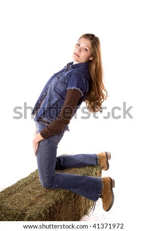 A woman kneeling on a hay bale while leaning back with a sexy look on her face while wearing denim.
