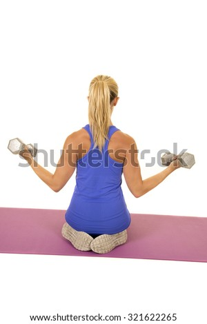 a woman kneeling with her back to the camera with weights. - stock photo