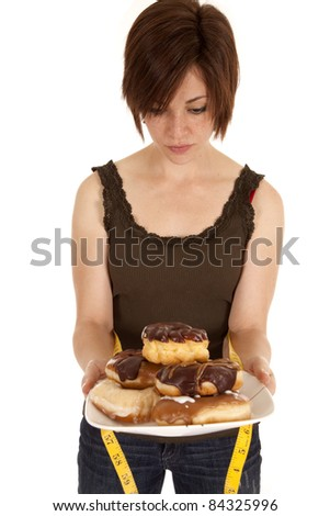a woman knowing that the pile of doughnuts will add inches to her waist. - stock photo