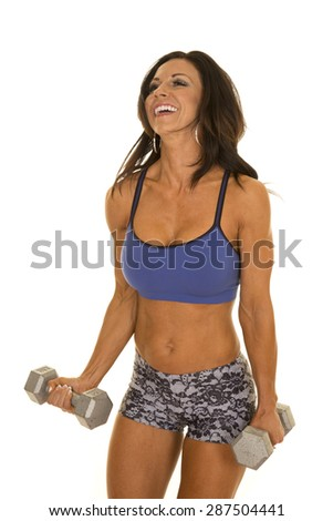 a woman laughing while working out with weights.