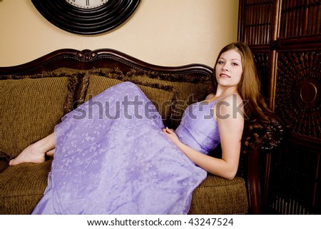A woman laying back in her purple formal with bare feet poking out with a small smile on her face. - stock photo