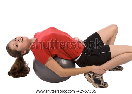 A woman laying back on a ball with a happy expression on her face. - stock photo