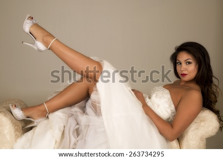 a woman laying back on a cream couch in her wedding dress. - stock photo