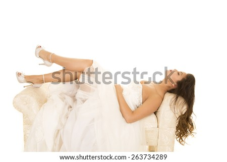 a woman laying back on her bench in her wedding dress with her feet up. - stock photo
