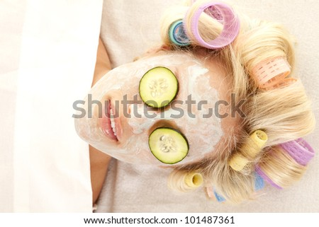 A woman laying down with curlers in her hair and a cream face mask. - stock photo