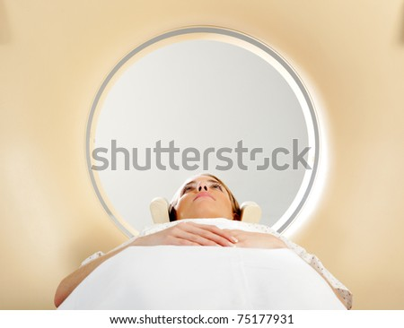 A woman laying down with eyes open having a CT scan - stock photo