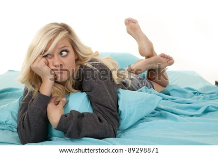 A woman laying in her bed being lazy. - stock photo